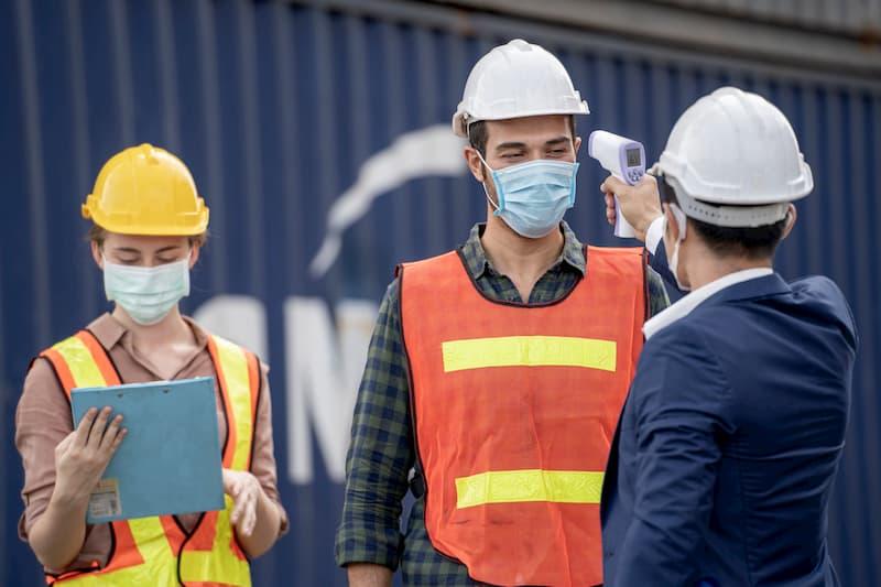Encargado midiendo la temperatura a un trabajador para evitar el covid